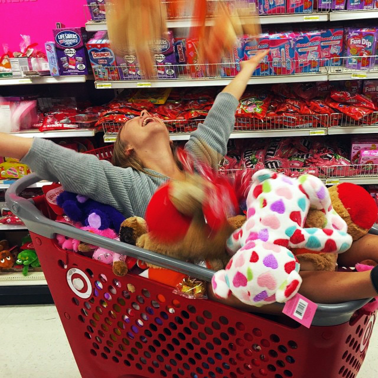 Marina Barnes in a red Target shopping cart and covered with plush animals, some of which she is tossing joyously into the air with her arms outstretched in celebration and her feet sticking out the end of the cart