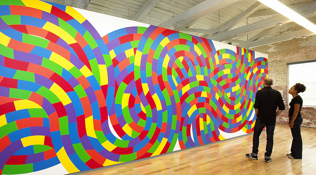 photo of 2 people standing before a large, curving, Sol LeWitt wall drawing