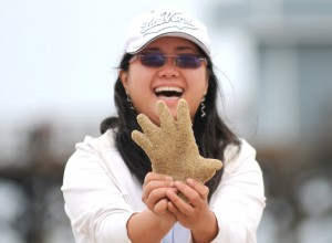 CSULB student on the beach at the Seal Beach Pier showing the plaster casting of her hand that she's just made.