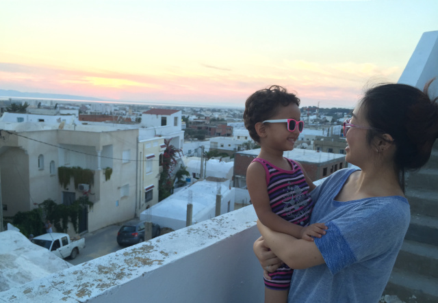 Grace Kim on a balcony and holding a child