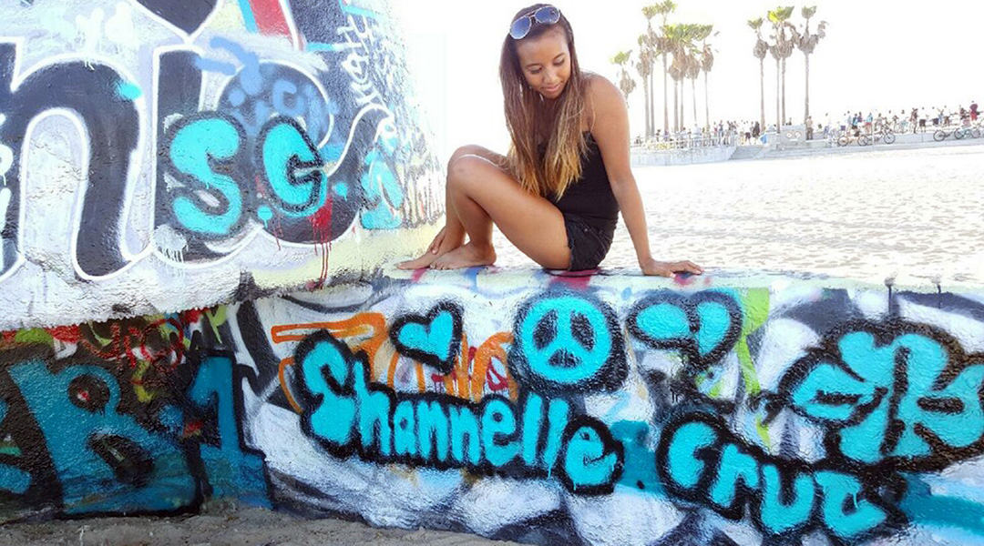 Shannelle Cruz sits on a low wall at Venice Beach, CA, where she's spray painted her name in vibrant blue letters with flowers