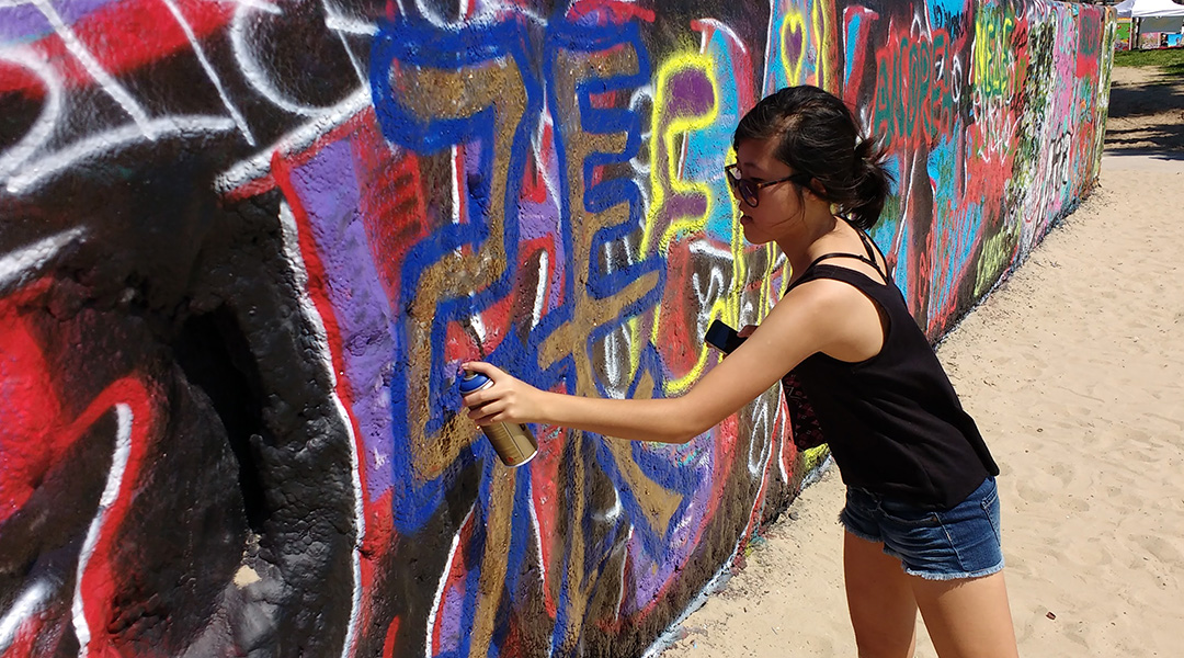 Stephanie Chang painting Chinese characters in gold with a blue outline on an art wall
