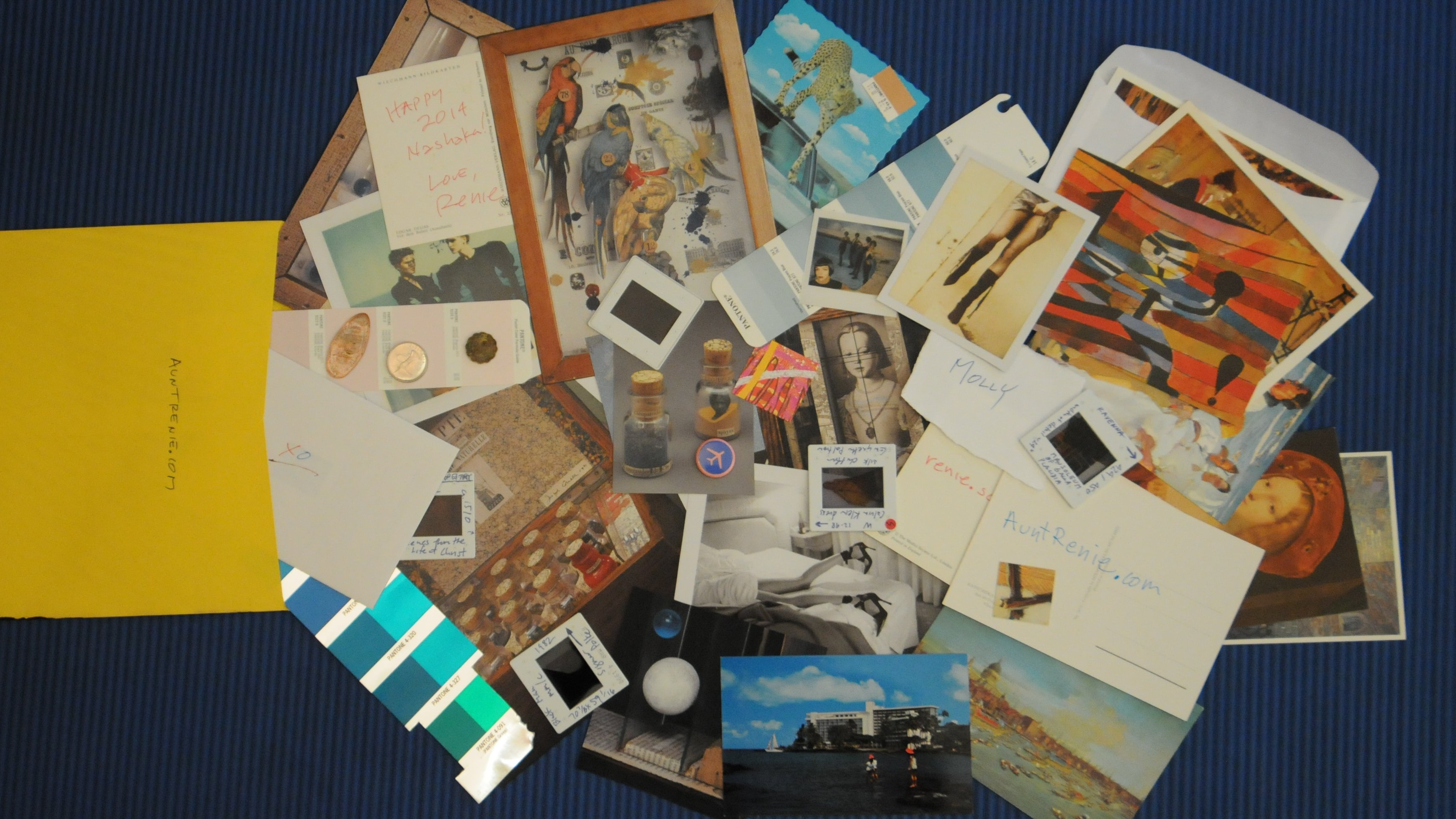 """an """"Art Care Package"""" - a large envelope filled with many bits of ephemera: photographs, slides, paint chips, audio CD's, foreign coins, and other materials"""